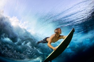 Surfer Stu Johnson duck dives his board to clear the rolling waves of the ocean at Cloudbreak, an outer reef in Fiji