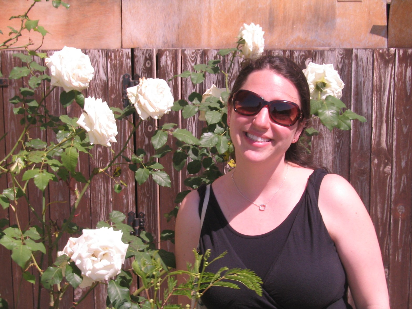 The Mint Chip Mama Long Island Mom Blogger in front of white roses in Crete, Greece