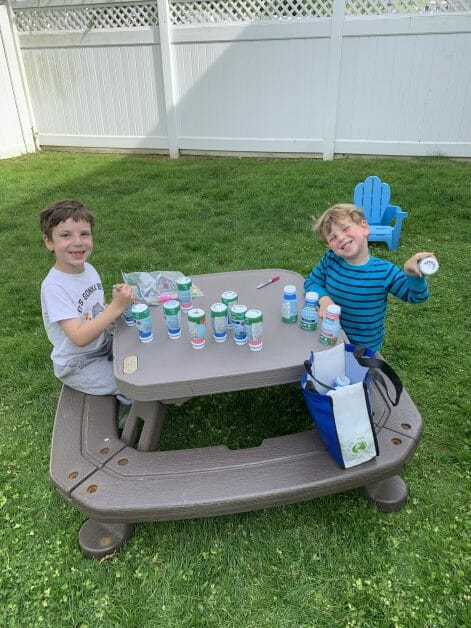 My boys - age 6 and 3 - sitting at a picnic table decorating the bottom, of recycled drinkable yogurt containers with Sharpies as markers for our garden