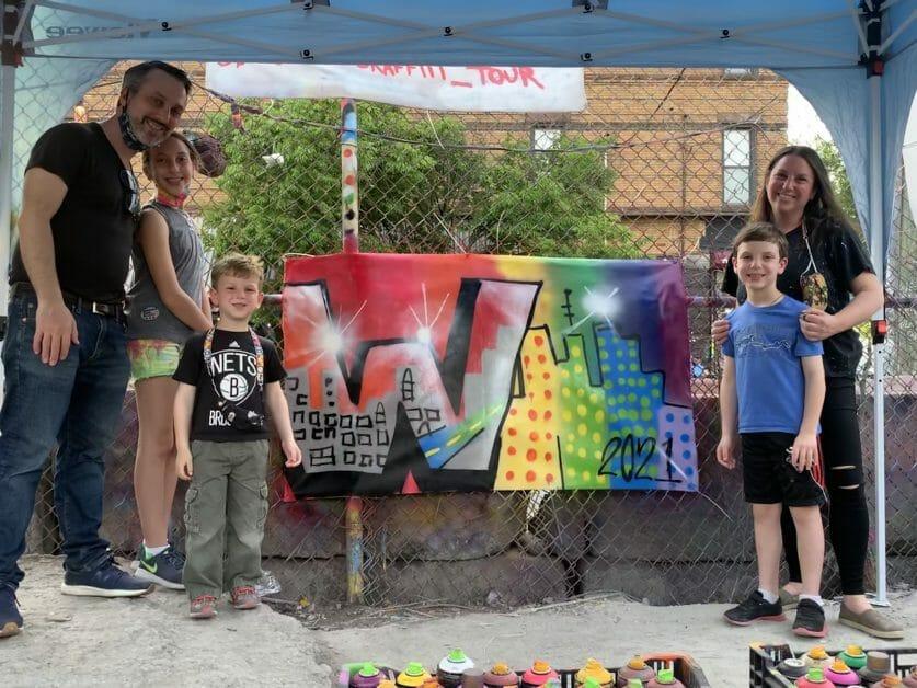 Family standing in front of the street art they just made in Brookylyn Unplugged Graffiti Street Art Workshop in Bushwick, Brooklyn