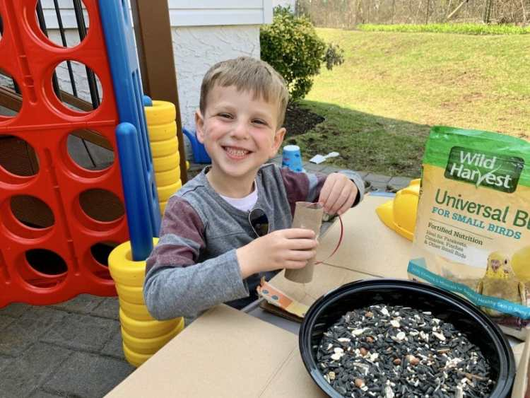 A little boy making bird feeders from recycled objects