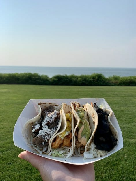 A hand holding Mattitaco tacos on the water in Greenport