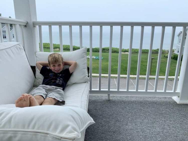 A little boy relaxing on the balcony in Greenport