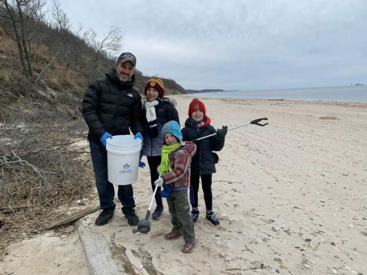 A dad and 3 kids at the 2021 1 day of the year beach clean up at Hallock State Park.