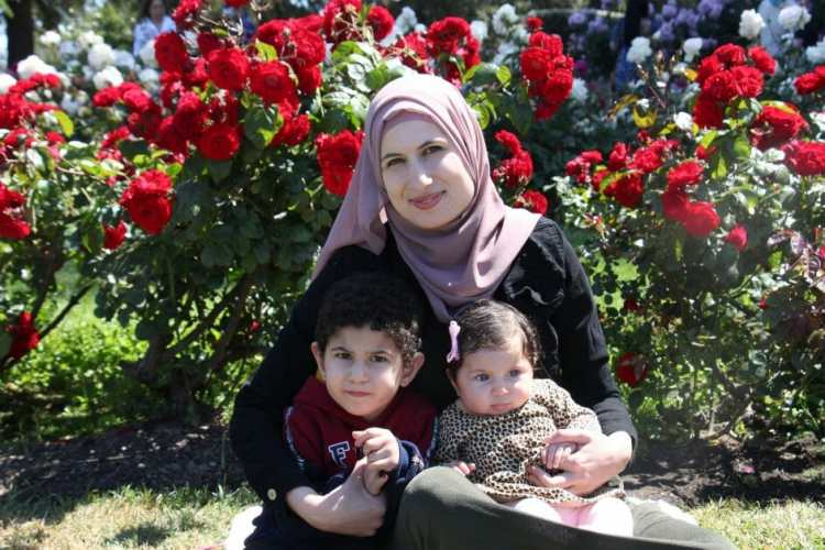 Mom with two small children in front of roses.