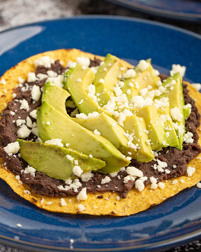 Avocado Tostadas #avocado #tostada #refriedbean #blackbean #cheese #cotija #easyrecipe #lunch #mexicanrecipe #salvadoranrecipe | The Missing Lokness
