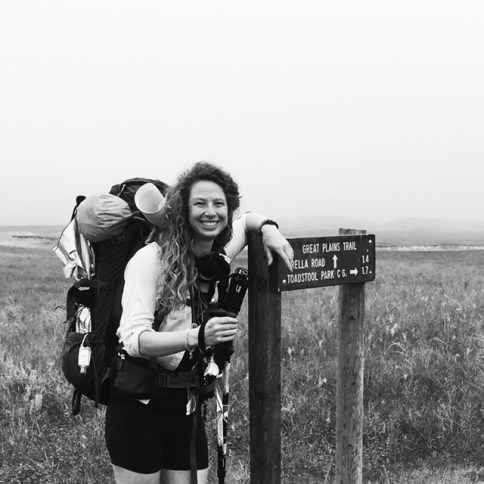 Black and white Emily next to hiking sign