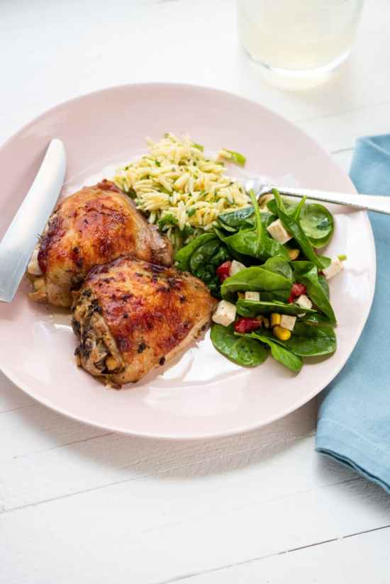 roasted chicken thighs on a pink late with orzo and spinach salad