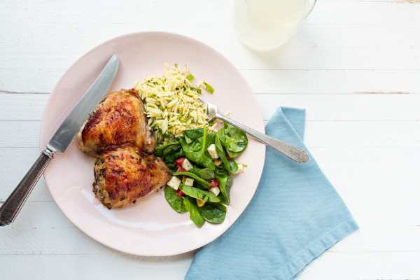 Greek Roasted Chicken Thighs on a plate with orzo and salad