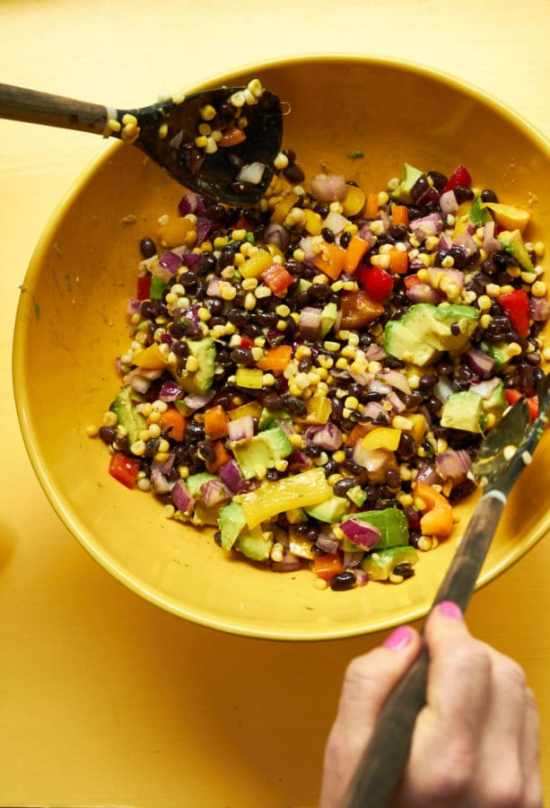 corn salad with black beans and vegetables being tossed in a yellow bowl