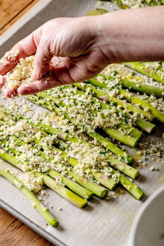 Spreading panko over asparagus on a baking sheet