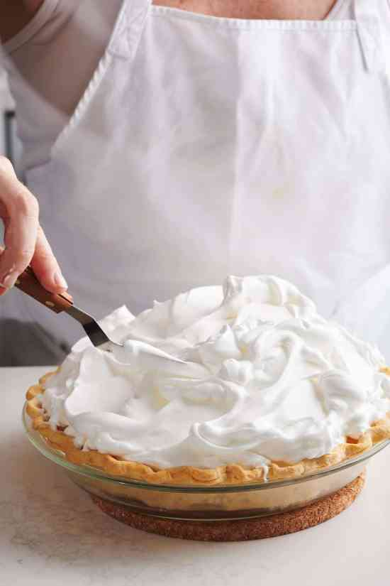 spreading meringue on a pie with an offset spatula