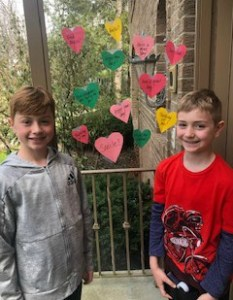 The Mom Huddle- It Could Be Worse Pandemic pic of boys putting hearts on neighbors door