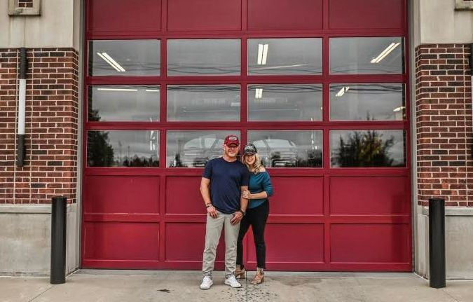 Woman, Mother, Breast Cancer Survivor- Cari with husband Matt standing linked arms in front of the firehouse door
