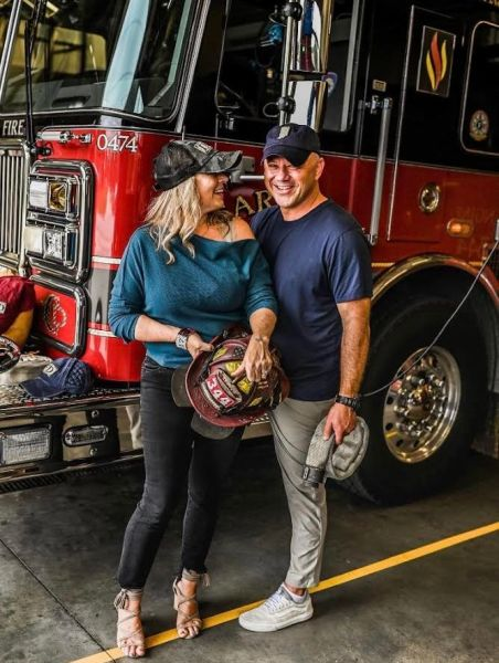 Woman, Mother, Breast Cancer Survivor- Cari and Matt standing by a firetruck with smiles