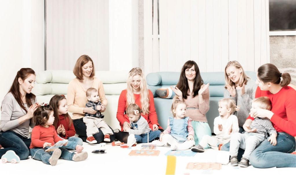 mommy and me class with a group of new moms and their babies playing, clapping hands