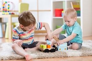 kids friends playing with crane car toy together
