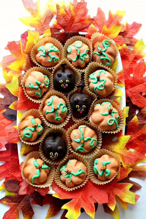 Peanut Butter Ball Pumpkins and Cats on a rectangular platter surrounded by artificial fall leaves