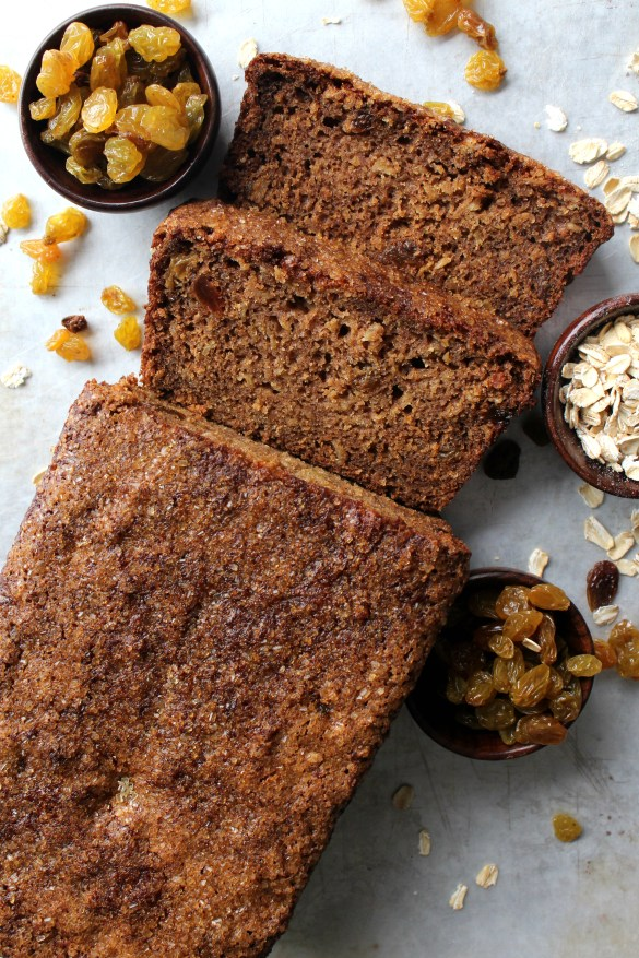 Oatmeal Raisin Quick Bread with two cut slices with little bowls of raisins and oatmeal