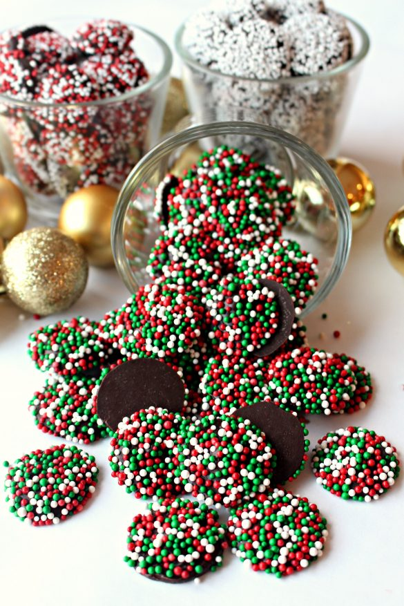 A tipped clear glass spilling out red and green sprinkled Nonpareil Candies