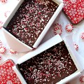 Two open tins filled with Peppermint Fudge with the red and white lids next to them