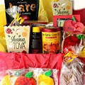 Rosh Hashanah gift care package box lined in red and yellow tissue paper and filled with homemade and purchased gifts with apples and honey flavors.