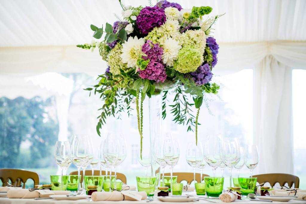 White and purple flowers in high table setting for wedding