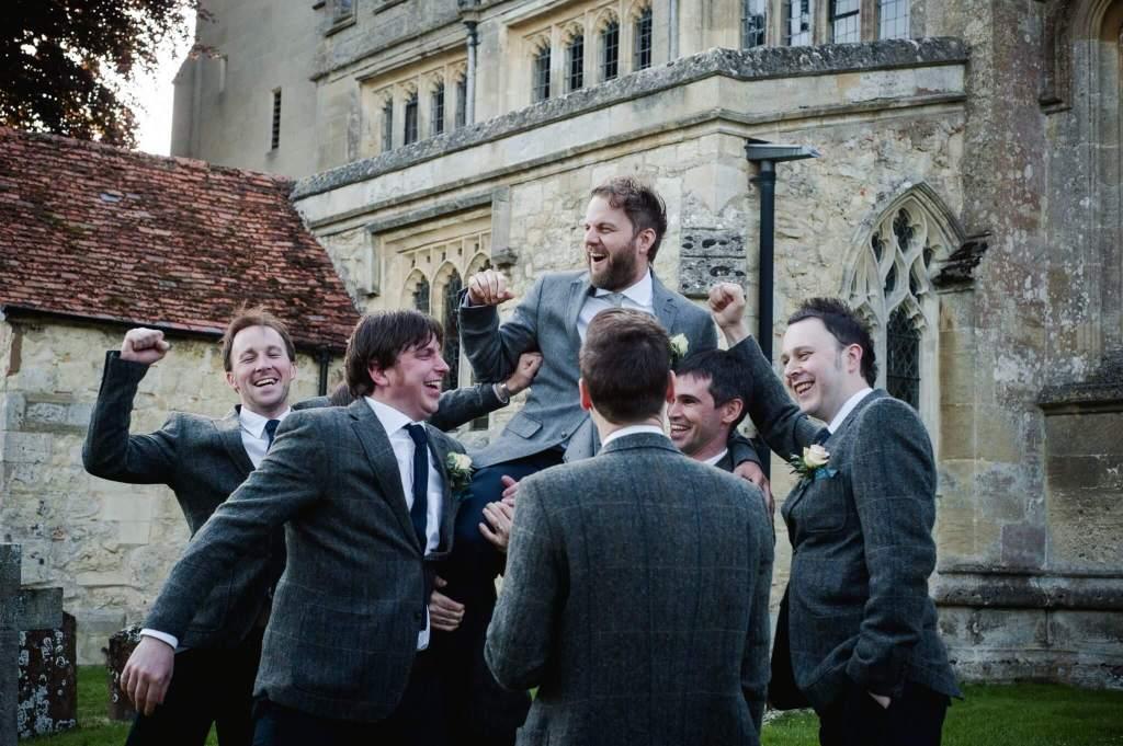 Ushers holding groom at wedding