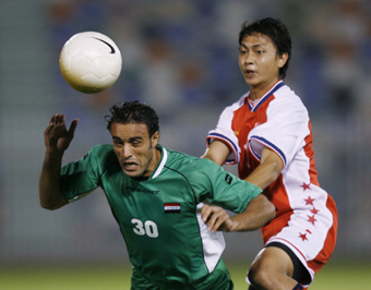 Muaad Saleem of Iraq fights for the ball with Shahril Ishak of Singapore during the 15th Asian Games 2006 Men's Group B first round soccer match in Doha