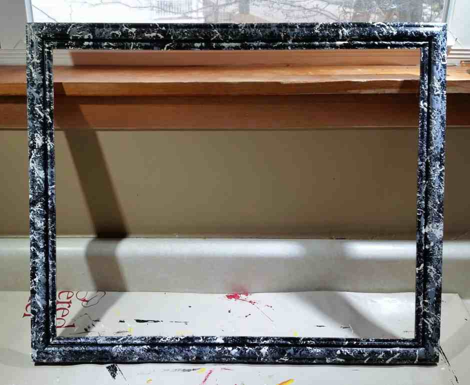 photo of how to upcycle a photo collage frame with black background with grey and white painted marble effect