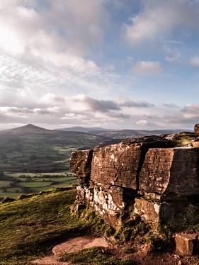 An outcrop of Rock on Ysgyryd Fawr with Pen y Fal behind.