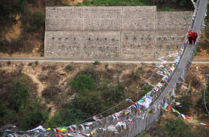 Monks walk on the Punakha Suspension bridge. Photo: Kaushik Naik