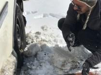 Mr. Sanju removing the snow stuck in the wheel; Photo: Abhinav Kaushal