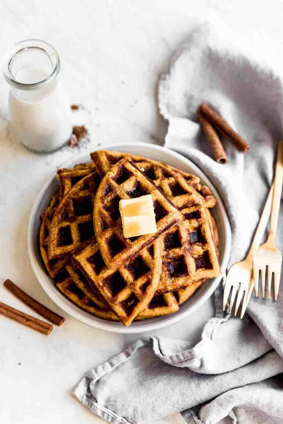 pumpkin waffles cut on a plate with butter on top and forks on the side