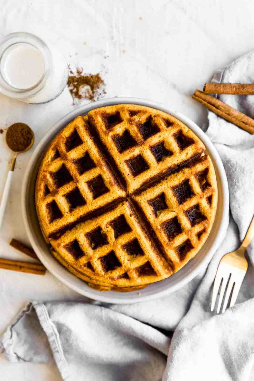 paleo pumpkin waffles stacked on a plate