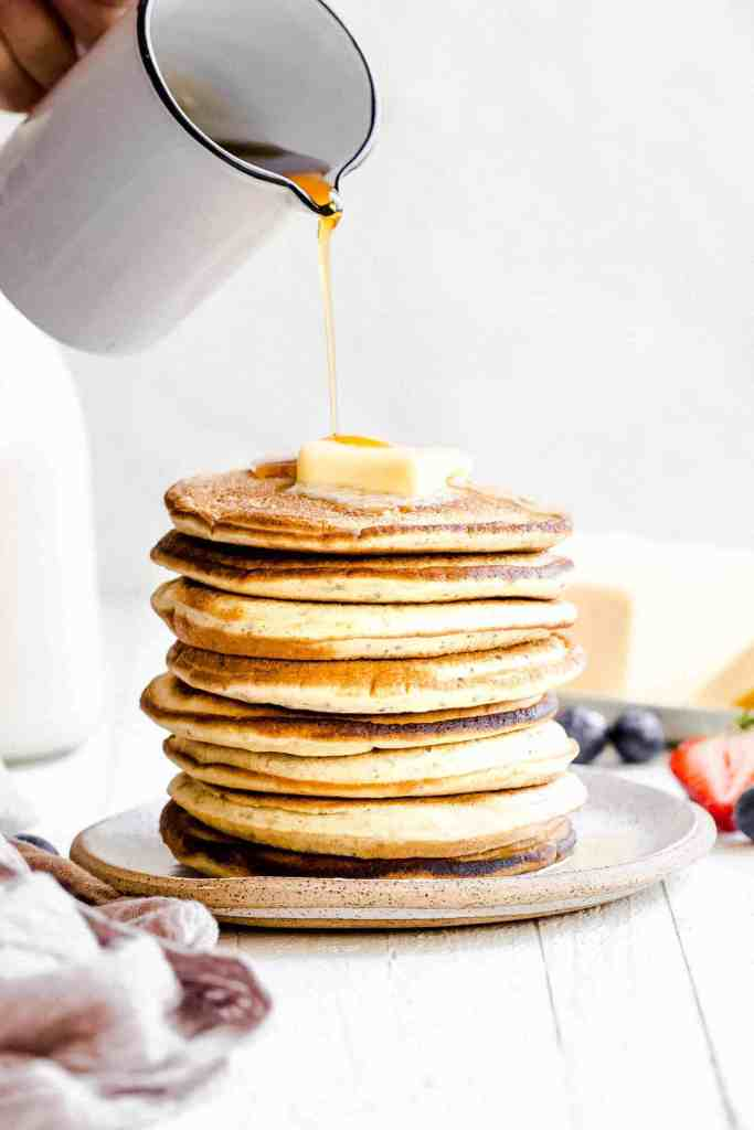 pouring maple syrup onto a stack of fluffy pancakes on a white plate