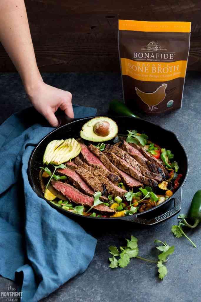 hand holding a cast iron pan full of steak fajitas