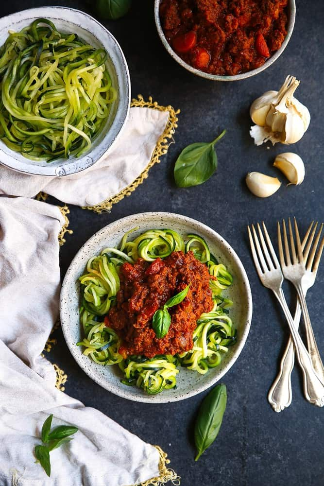 A zucchini noodle Whole30 Bolognese recipe that's healthy! Made with nutrient dense bone broth, healthy vegetables and grass-fed beef and bacon- delicious! #whole30recipes #whole30 #paleo #bolognese #lowcarb
