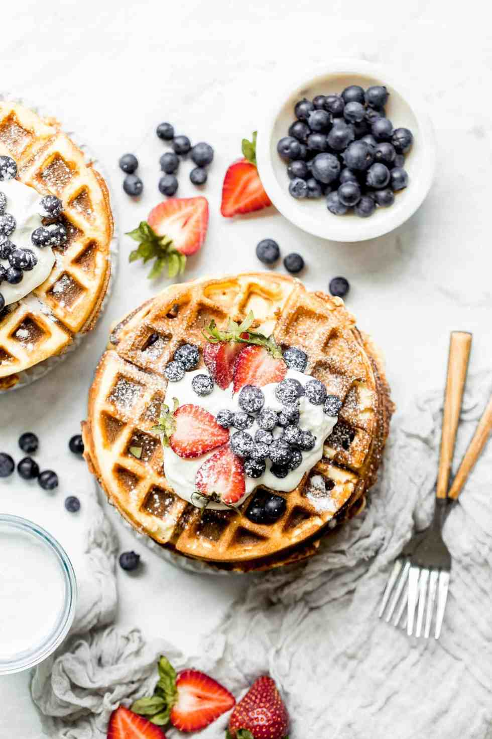 two stacks of paleo waffles on plates with berries