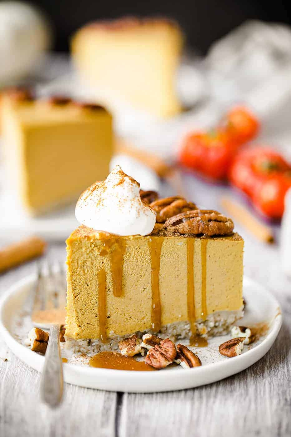 a slice of pumpkin cheesecake on a white plate with pecans, caramel sauce and whipped cream