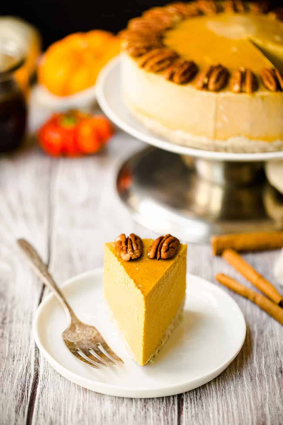 a slice of vegan pumpkin cheesecake with pecans on a white plate with a fork on the side