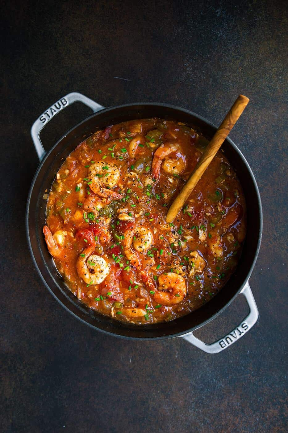 overhead shot of gumbo in a pot with a wooden spoon