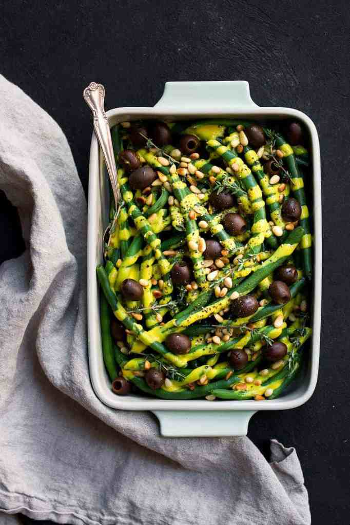 A perfect side dish for your Thanskgiving table or really any time of the year are these green beans with dairy free pumpkin alfredo and olives. Paleo thanksgiving recipes.