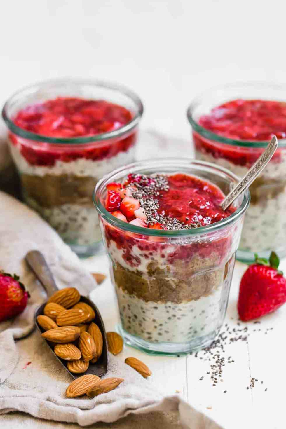 three jars of overnight oats with jam and chia seeds on top
