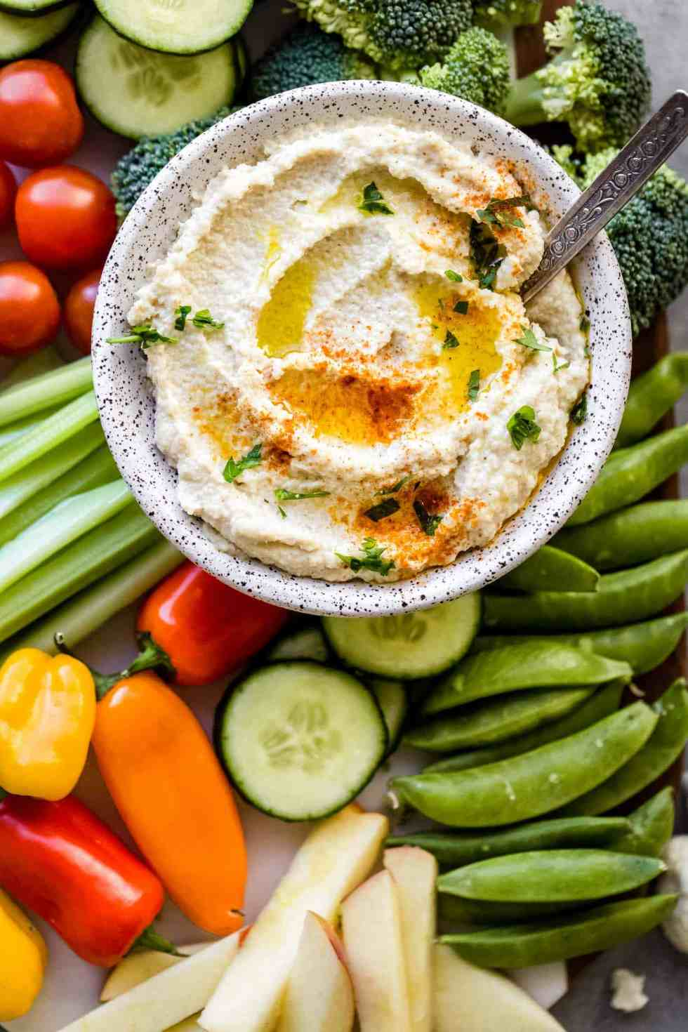 close up overhead shot of cauliflower hummus in a bowl with a spoon