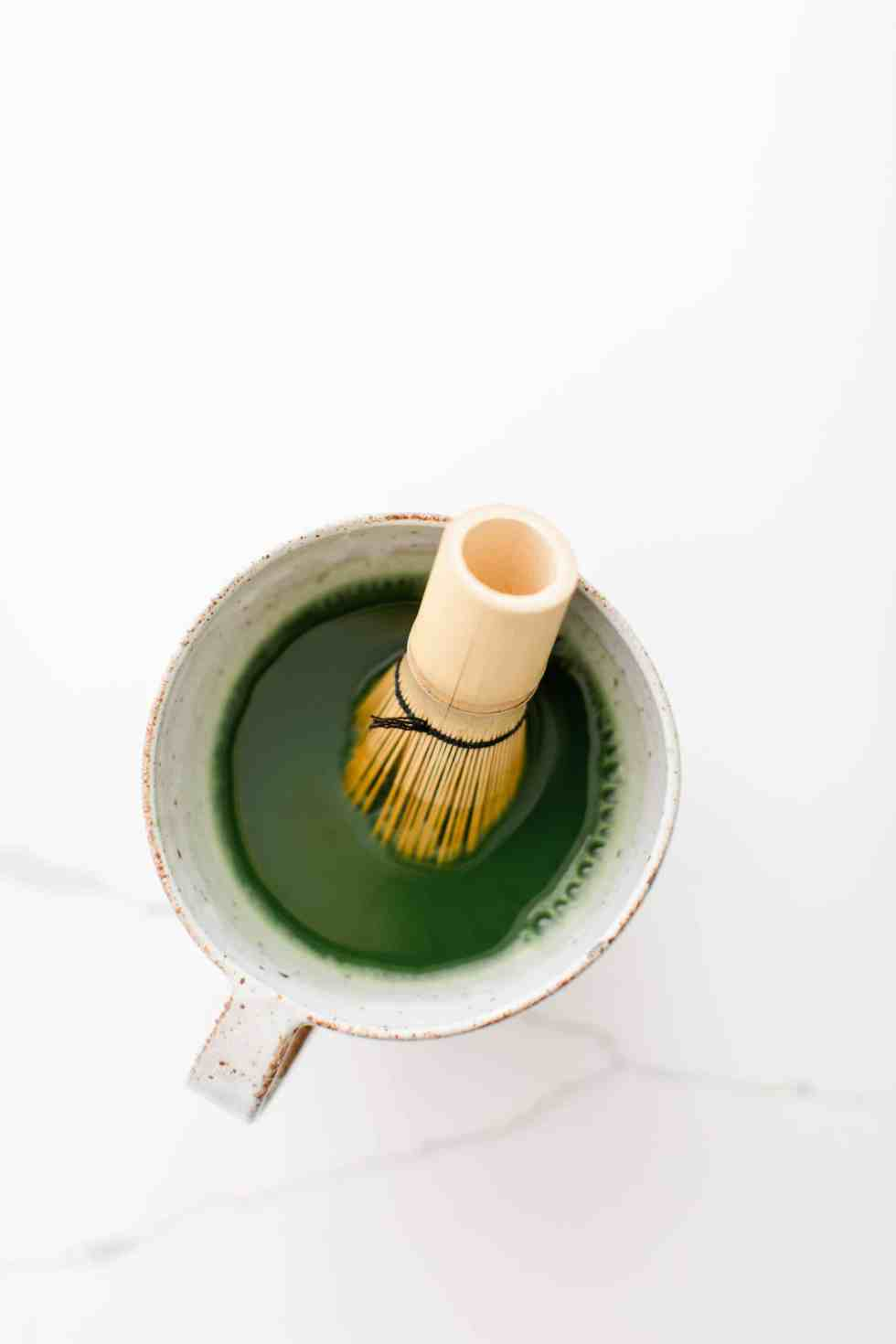 overhead shot of matcha tea in a mug with a whisk