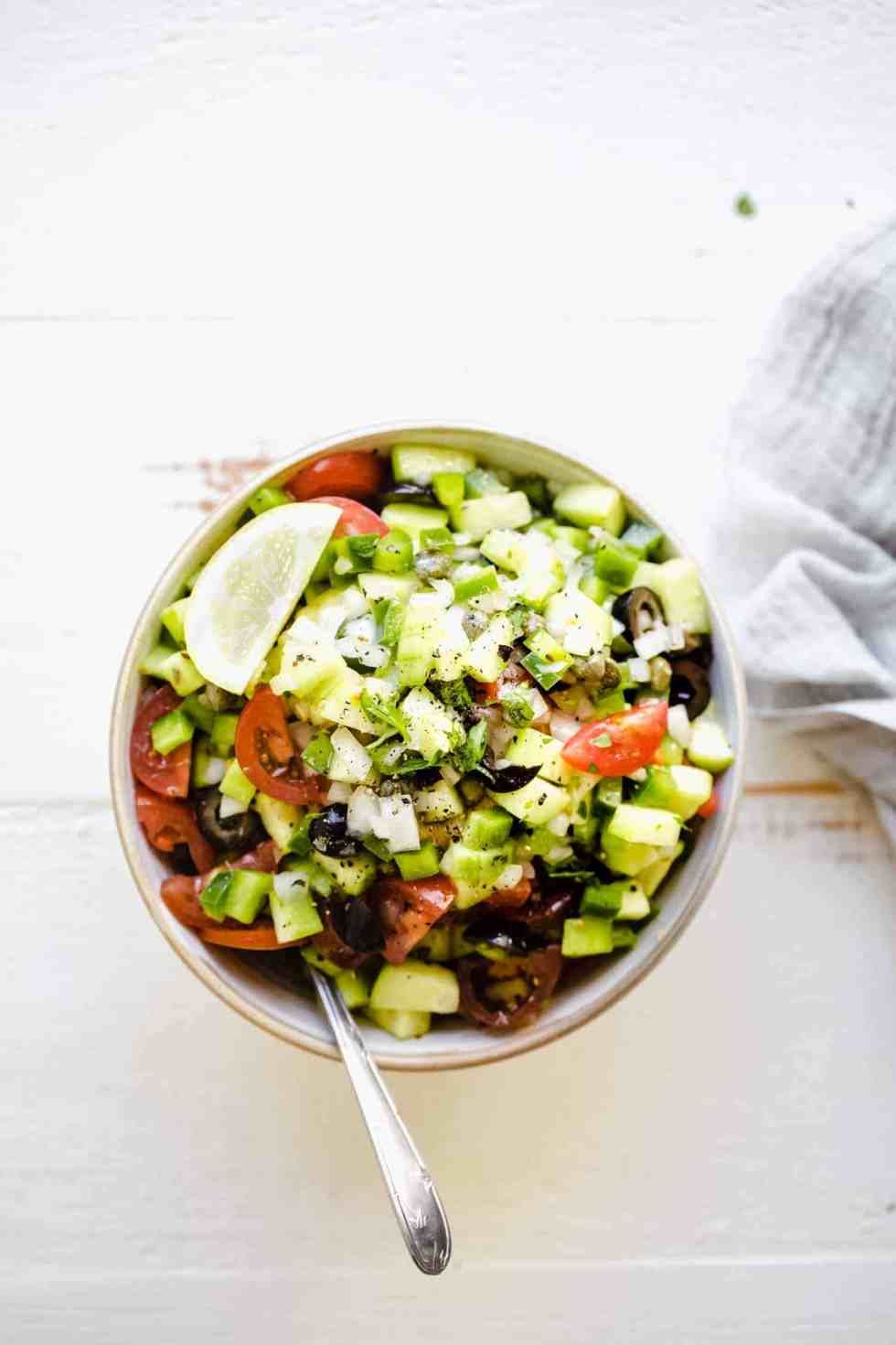 overhead of greek salad in a bowl with a spoon and lemon wedge