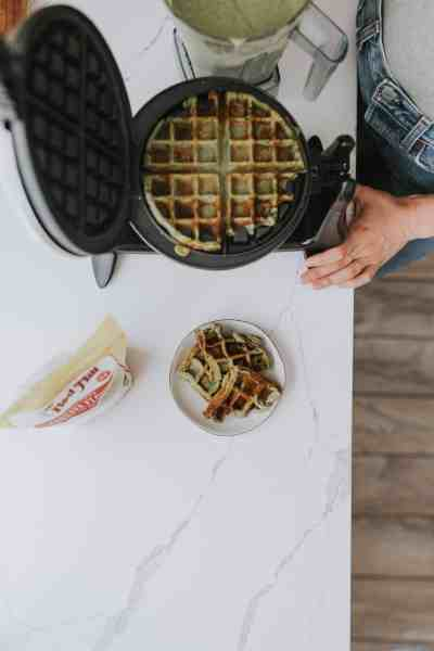 overhead of spinach waffles cooking in a waffle iron