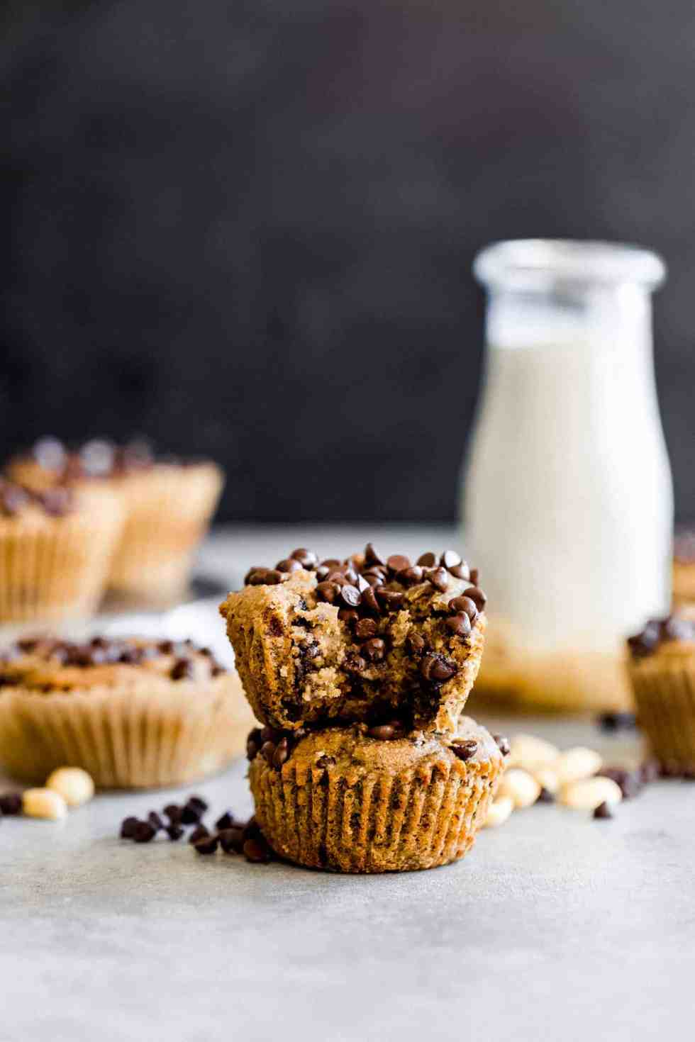 peanut butter banana muffins with dark chocolate chips stacked with a milk jug in the background