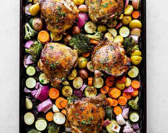 chicken thighs on a bed of veggies on top of a baking sheet